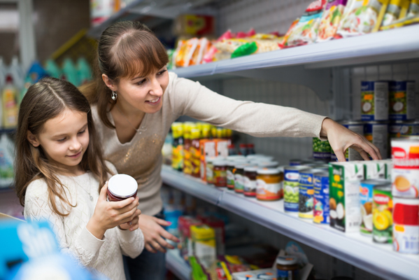 Mother and daughter selecting canned goods