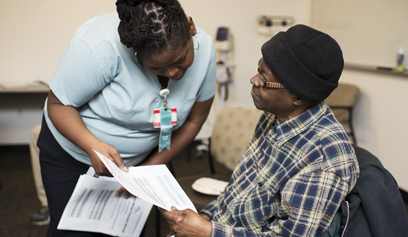 Codman employee helps a patient with paperwork