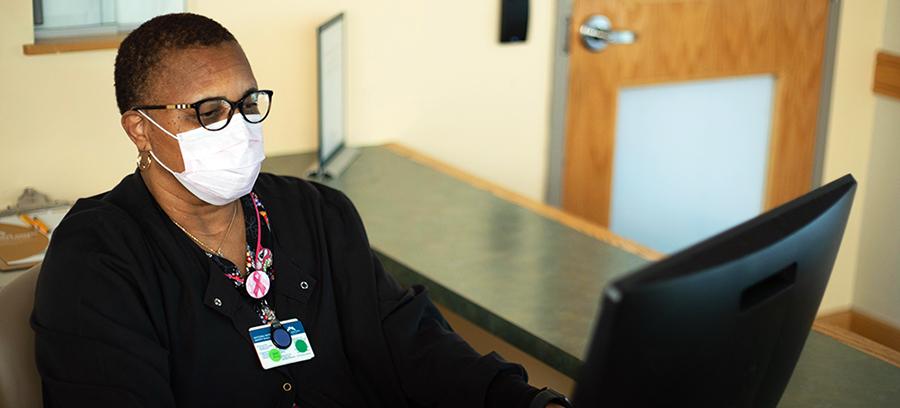Masked staff memeber at Registration Desk